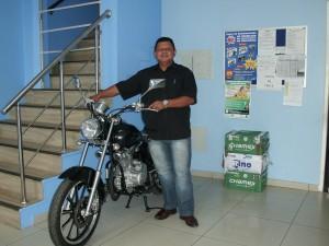 O diretor Ricardinho, mostrando a moto que será sorteada dia 28, no Sambódromo.